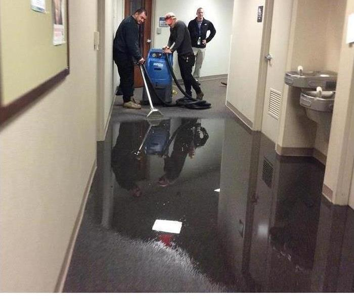 hallway filled with water with 3 technicians working to extract it